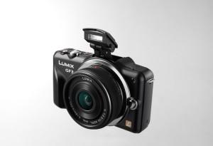 Panasonic Lumix DMC-GF3 - schwarz, von vorn, seitlich von oben mit Pancake 14mm, ausgeklappter Blitz (Bild: Panasonic)